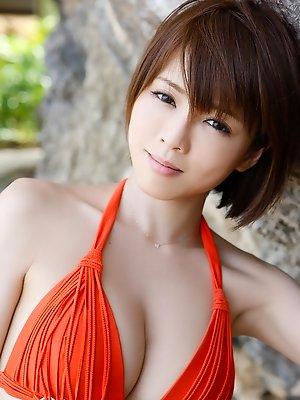 Yumiko Shaku Asian in orange bath suit takes a walk on the beach